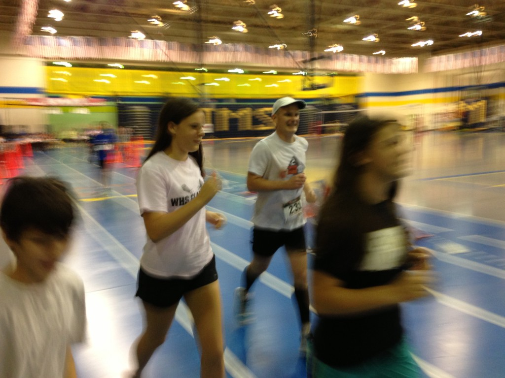 Centreville's Eric Setash runs his bell lap of the Grant Pierce Indoor 50k flanked by his children. Photo: Charlie Ban