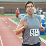 Tyler Cole glances at the clock as he finishes the mile at the DC Road Runners Track Championships. Photo: DC Road Runners