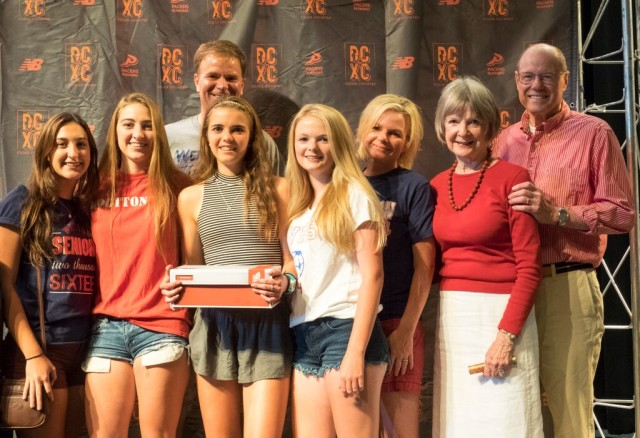 Grace Dallapa (holding the shoe box) surrounded by family and teammates at the 2015 All-RunWashington pep rally. She was on the All-Maryland team for the second year in a row. Photo: Roger Colazzi