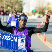 Sam Chelanga breaks the tape at the Cherry Blossom Ten Mile Run as the first American champion in 33 years. Photo: Dustin Whitlow