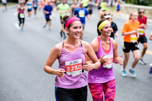 Christina Wryter and Lindsey Bernal grin their way down Rock Creek Parkway at the Navy-Air Force Half Marathon. Photo: Dustin Whitlow/DWhit Photography