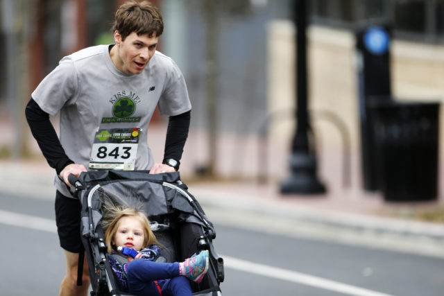 "Adam Schwaber pushes his daughter Julia up Wilson Boulevard at the end of the Four Courts Four Miler. ""Julia kept asking me why I was slow and told me to go faster,"" he said. ""I don't usually take her out on training runs, but for races that my wife and I both want to run, I usually bring Julia along in the stroller."" Photo by Brian W. Knight/Swim Bike Run Photography"