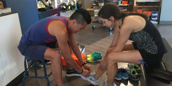 Bilig Bayar helps a customer into a pair of Nike Air Zoom Vomeros at the Clarendon Pacers. Photo: Charlie Ban