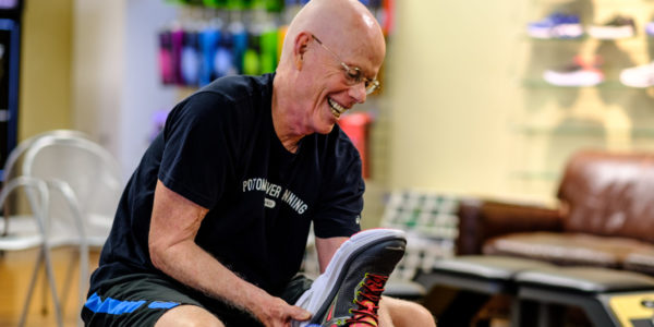 Chris Kelly helps fit a customer during his last shift at 7516 Leesburg Pike before his Potomac River Running store moves to Vienna. RunWashington photo by Dustin Whitlow