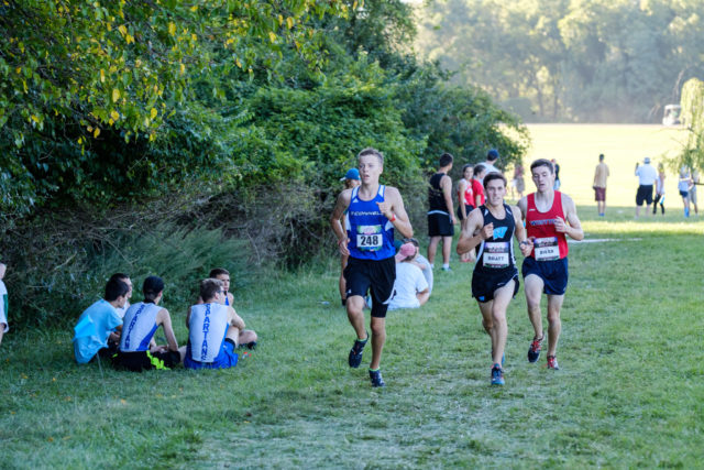 Max Grecyn runs alongside Aaron Bratt and John Riker in the third mile of the junior boys' race. Photo: Dustin Whitlow/DWhit Photography